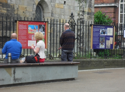 People having lunch outside the library, reading the panels