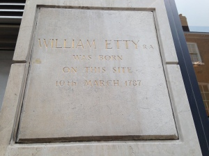 This plaque marks the site of the house on Feasegate where William Etty was born. It is located on the wall between the rear entrance of BHS and Viewpoint Opticians.